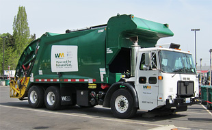 Photo of large green refuse truck, with sign that reads propelled by natural gas.