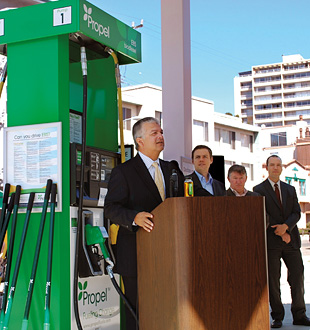 Photo of four men in suits standing behind a podium , giving a press conference at a fueling station in front of a fuel pump that dispenses ethanol and biodiesel.