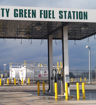 Photo of a fueling station with large biodiesel tanks in the background. A sign on the fuel canopy reads, Monroe County Green Fuel Station.