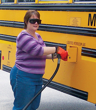 Driver Sandy Fecteau fuels one of MSAD 6's 10 propane school buses. <em>Photo from Maine School Administrative District No. 6, NREL/PIX 21778</em>