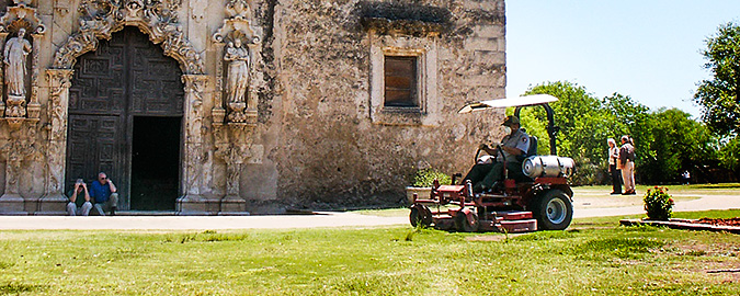 A man operates a commercial-size propane mower in front of a historic mission.