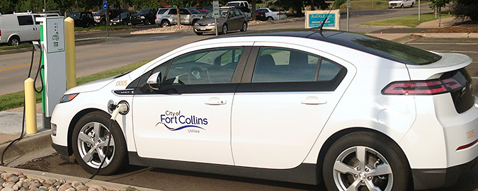 A Chevy Volt sedan is plugged into a charging station in a parking area outside the City of Fort Collins fleet facility.