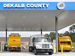 Three refuse haulers filling up at a natural gas fueling station.