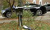 Photo of an electric vehicle connected to a curbside charger on a residential street