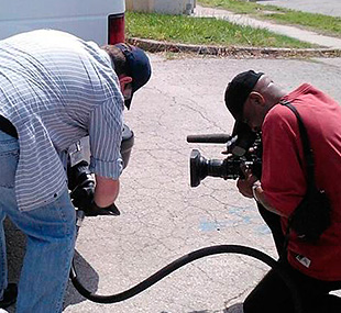 This photo shows a man with a camera filming another man refueling a propane van.