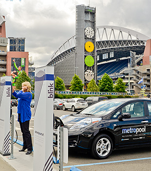 This photo shows a driver plugging in one of King County Metro Rideshare Operations electric vehicles.