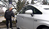 Photo of a man plugging an electric vehicle into a charging station.