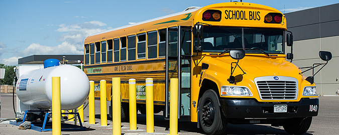 A photo of a yellow school bus parked next to a white propane tank.