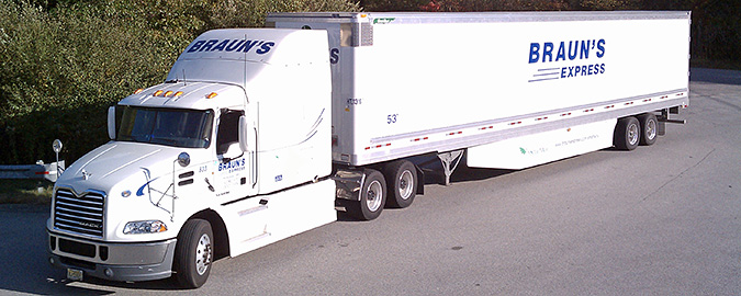 A photo of a white semi-truck with the side of the truck labeled