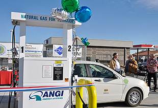Photo of a white car parked in front of a white CNG fueling station with balloons tied to the top.