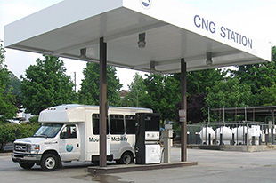 Photo of a white shuttle bus parked in front of a refueling station for CNG.