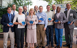 Photo showing a group of men and women holding circular blue awards.