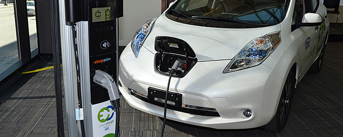 A photo of a white PEV plugged into a charging station.