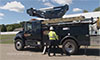 Photo of a man standing in front of a hybrid utility truck