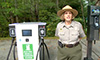 Photo of a female national park ranger next to a DC charger.