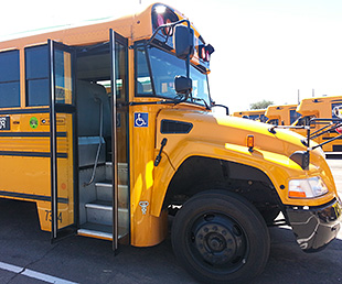 Photo of a yellow school bus with the door to the bus open.