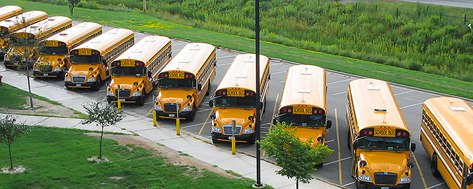 Photo from above showing a row of yellow school buses parked below in a parking lot.
