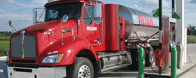 A photo of a red Class 8 truck filling up at a compressed natural gas station.