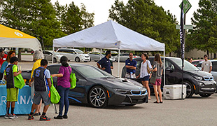 A photo of a people gathered around an electric vehicle under an outside canopy.