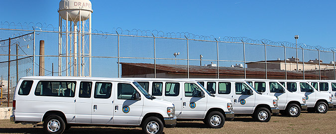 Picture of five white propane-fueled vans in front of prison with barbed wire fence and water tower that says