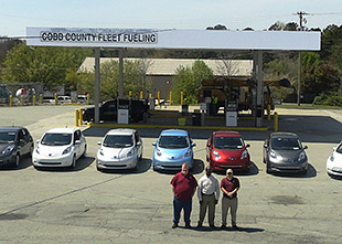 A photo of three men standing in front of seven cars with a fueling station in the background.