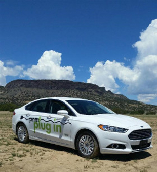 A photo of a PNM plug in electric vehicle in front of a mesa.