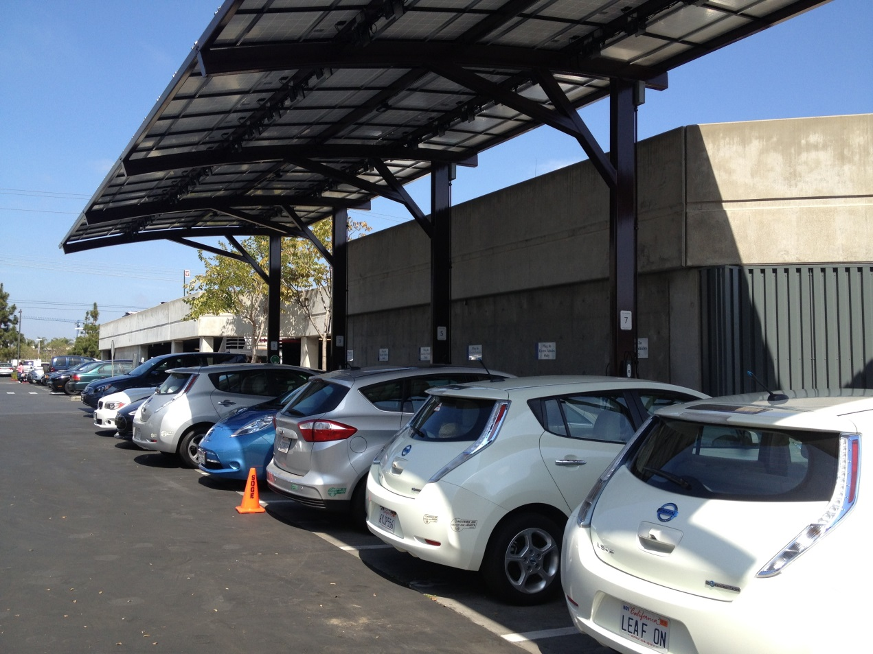 Plug-in electric vehicles (PEVs) parked under a solar canopy with access to electric vehicle supply equipment.